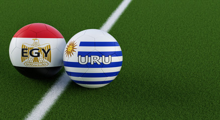 Uruguay vs. Egypt Soccer Match - Soccer balls in Uruguays and Egypts national colors on a soccer field. Copy space on the right side - 3D Rendering