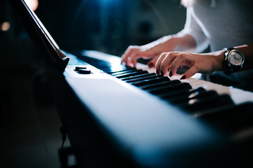 Close-up image of a female hands playing piano synhtesizer.