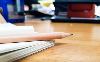 Brown Pencil and White Notebook on office concept background