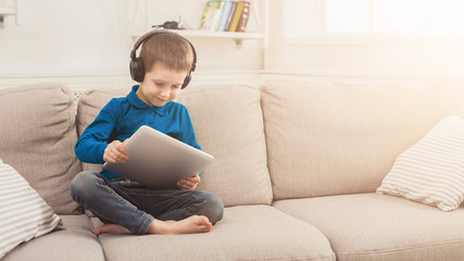 Little boy using digital tablet on sofa at home