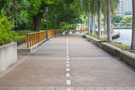 Concrete path way in public park. text space.
