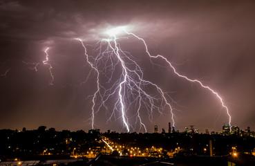 Foto op Plexiglas Zalm Lightning over city skyline