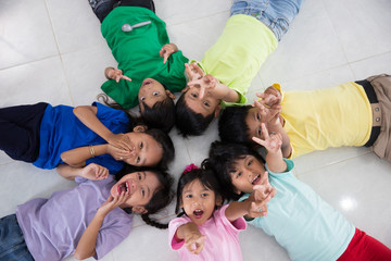 excited young little kids group laying down