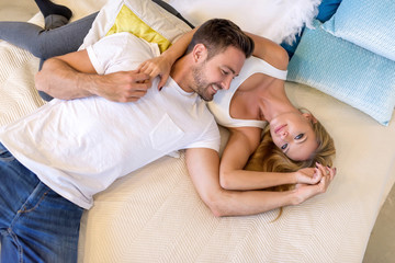 A handsome young man lying on the bed with head on his girlfriends chest.