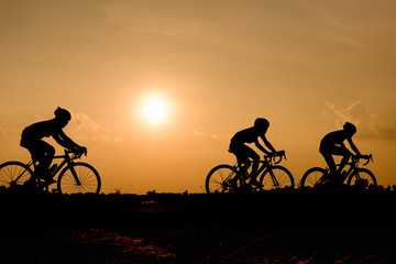 Silhouette of cycling on sunset background.