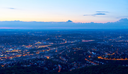 Night falls over Stuttgart City in Germany / Turning on the lights in the city