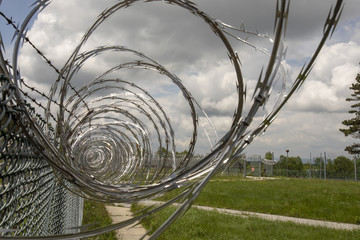Prison yard fencing with razor wire