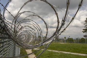 Prison yard fencing with razor wire