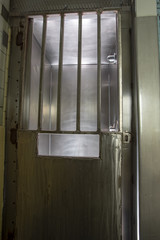 Metal door with bars on shower stall in prison