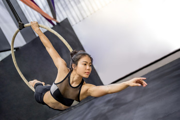 Foto auf Leinwand Gymnastik young asian acrobatic woman doing her gymnastics performance on aerial hoop or aerial ring
