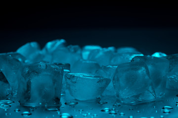 Ice cubes in turquoise color on a black background with drops of water