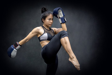 Young Asian woman boxer with blue boxing gloves kicking in the exercise gym, Martial arts on black background