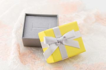 Small yellow and gray jewelry gift box with bow on lace background