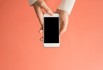 Female hands using smartphone black screen with orange background from top view. Communication concept.