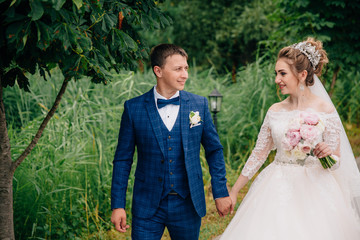 The portrait was just married and walking in the garden. A man looks at his wife lovingly and leads her by the hand. The girl believes her beloved and follows him.