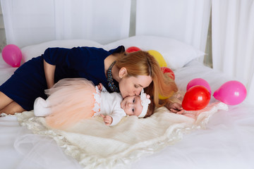 A woman with white hair in a blue dress kisses her little daughter lying on the bed. The girl pulls the pens to the side.