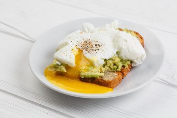 Toast and poached egg with avocado on a plate on white wooden table