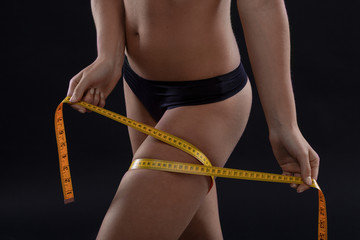 slimming woman measuring her attractive leg on black background