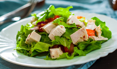 fresh vegetables salad with chicken and onion, lettuce, tomato in white plate on table