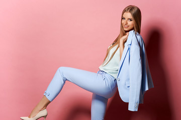 Beautiful fashionable girl with long blonde straight hair in a blue jacket and trousers. Girl in the studio on a pink background. Advertising, hair products, beauty salon, cosmetics, clothing. Wall mural