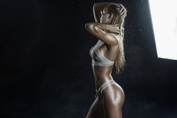 Beautiful wet athletic big breasted blonde girl wearing white sexy translucent bikini posing in falling water drops of rain on black background