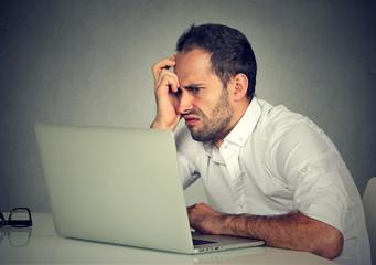 Negative man using laptop in anger