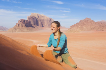 young woman with a smile sprinkled sand in the desert