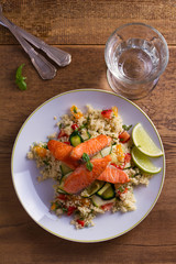 Salmon with tomato couscous, zucchini and lime. View from above, top studio shot