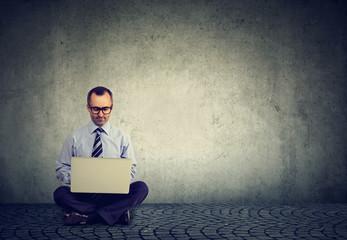 Hardworking man using laptop on gray