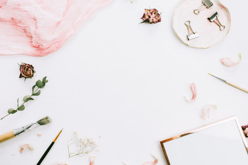 Frame with space for text of photo frame, pink blanket, eucalyptus branches and rose flowers on white background. Flat lay, top view still life artist blog hero header.