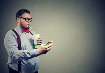 Obese man with soda and phone