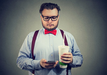 Obese man with sweet soda and phone