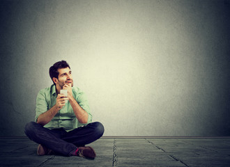 Pensive man sitting in floor with phone