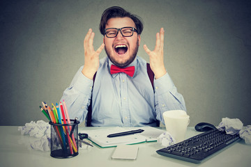 Stressed man screaming at workplace