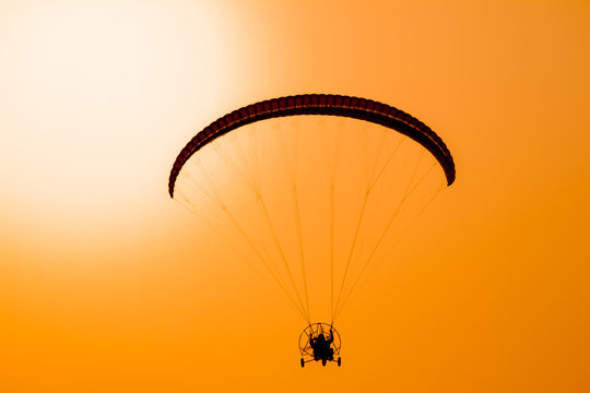 Paraglider flying with paramotor on dramatic sunset sky with big sun in orange and yellow. Concept for adventure extreme ultra light aviation