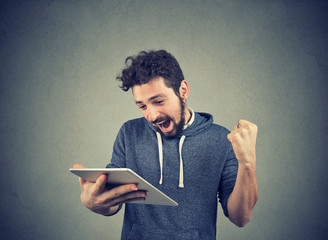 Happy man with tablet holding fist up