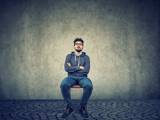 Pensive hipster man on chair