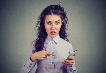 Amazed woman pointing at phone