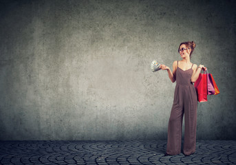 Trendy woman with shopping bag and money