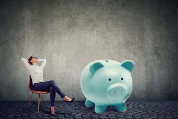 successful business woman with big piggy bank relaxing sitting on chair