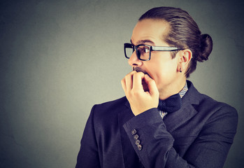 anxious young man biting his fingernails looking to the side