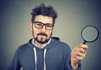 Curious man investigating with magnifier