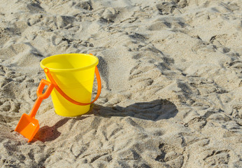 yellow child's plastic sand pail with orange shovel on a sunny summer day at the beach with copy space