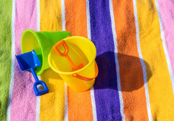 2 child's plastic sand pails and shovels with a colorful striped beach towel on a sunny summer day