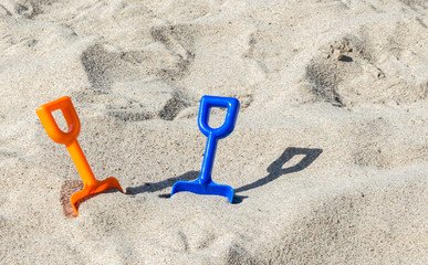 two small plastic shovels stuck in the sand at a beach on a sunny summer day