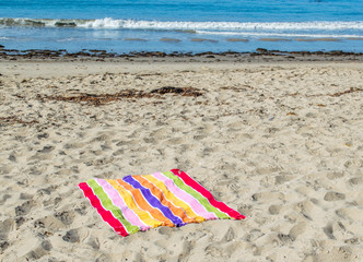 colorful striped beach towel spread out at an empty beach on a sunny summer day with the ocean in the distance
