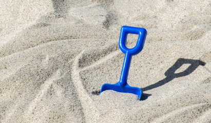 small blue plastic shovel stuck in the sand at a beach on a sunny summer day