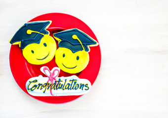 3 colorful graduation cookies on a red plate on a wooden table