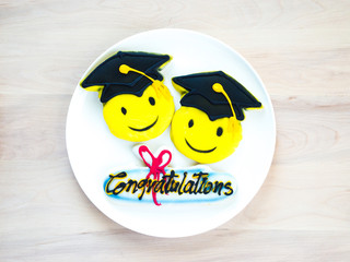 3 colorful graduation cookies on a white plate sitting on a pale wooden table