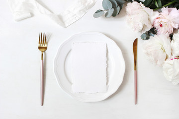 Feminine wedding, birthday desktop mock-up scene. Porcelain plate, blank craft paper greeting cards, silk ribbon, golden cutlery, eucalyptus, peony flowers. White table background. Flat lay, top view
